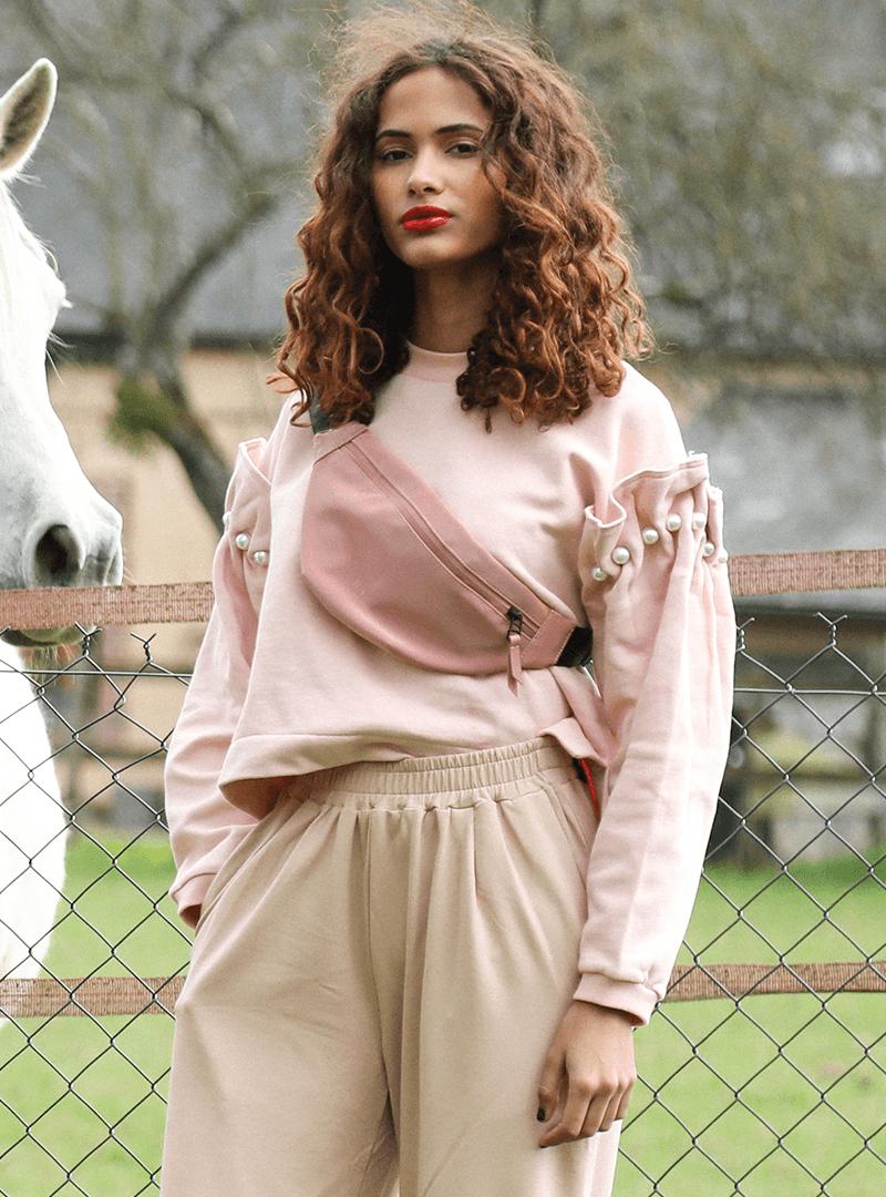 femme portant un sweat rose un sac banane rose et un pantalon beige mother of pearl sanna conscious concept