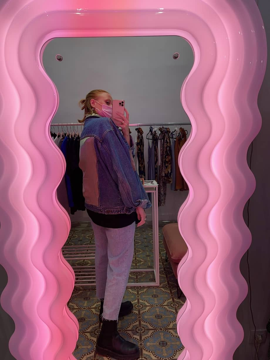 sanna taking a picture in a pink mirror while wearing a vintage upcycled denim jacket from anotherland and a jean archive 5 Ways to Style our SANNA x Anotherland Upcycled Vintage Denim Jacket sanna conscious concept