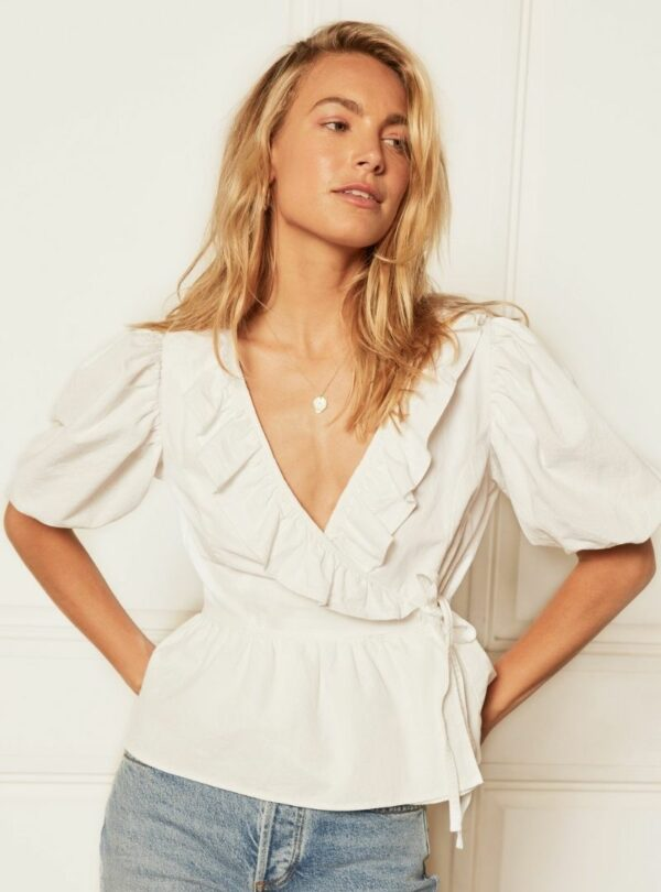 woman wearing the romeo puff sleeve blouse in white boyish jeans sanna conscious concept